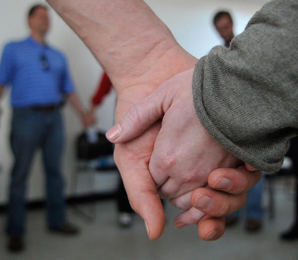 Students hold hands at the end of a recovery meeting at Kennesaw State University with students in recovery from addiction as they say the Serenity Prayer to close the meeting.