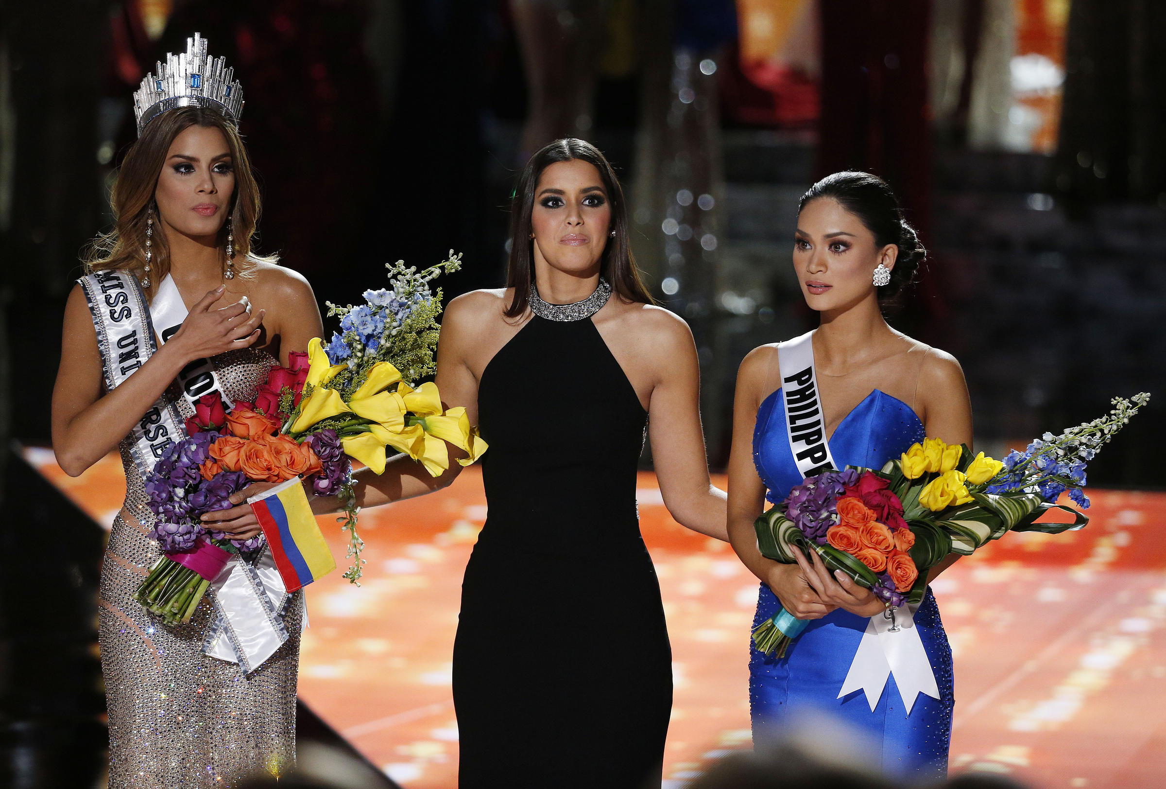 94705aa8f2 Former Miss Universe Paulina Vega, center, reacts before taking away the  flowers, crown and sash from Miss Colombia Ariadna Gutierrez, left, before  giving ...