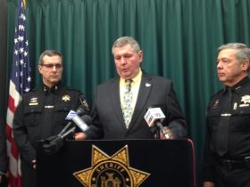 Onondaga County Deputy Chief John Balloni (left) and Undersherrif Warren Darby (right) look on as Sheriff Kevin Walsh announces his future plans.