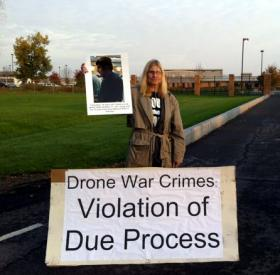 a protestor holds up signs saying violation of due process at air base