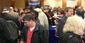 Job seekers crowd into a job fair earlier this month where many employers had active openings.