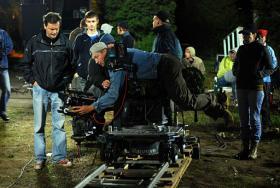 Set photo of a camera man adjusting equipment at night