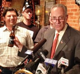 Sen. Chuck Schumer reveals the bottle that could soon hold beer grown from ingredients grown by Empire Brewing Co. on its farm in Cazenovia.  Owner David Katleski is at left.