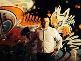 Small Plates Detroit, GM Andrew Belair standing in front the restaurant's Graffiti Wall.
