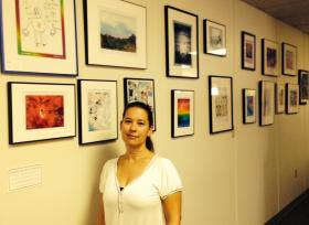 Loren Cunningham stands in front of a wall of artwork by survivors of sexual assault and abuse.