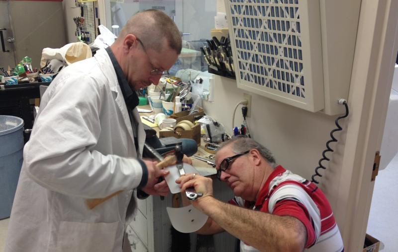 Jeremy Hall of Rehab Tech hammers fittings into a leg brace fabricated right at their offices