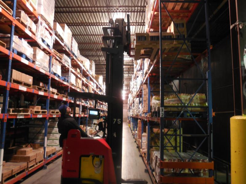 a forklift moves items on a top shelf in an industrial warehouse aisleway