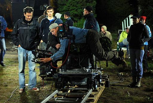 Set photo of a camera man adjusting equipment at night