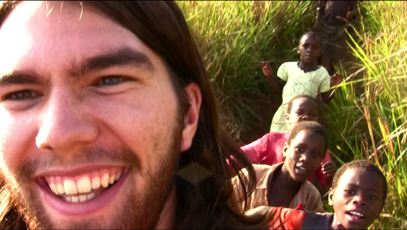 smiling close-up of Peterka, with four african children in the background candid