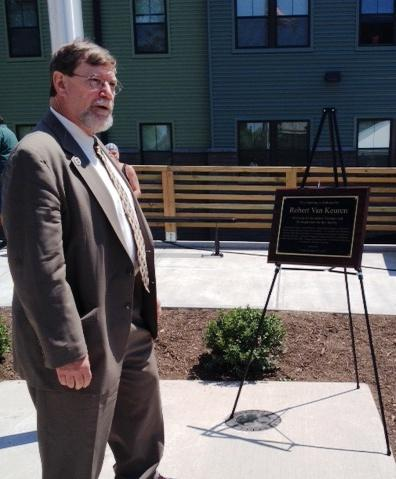 The building's namesake, Robert VanKeuren stands in front of the plaque dedicating it in his honor.