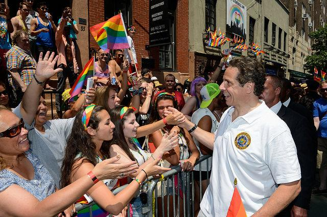 governor shaking hands with bystanders at the pride parade