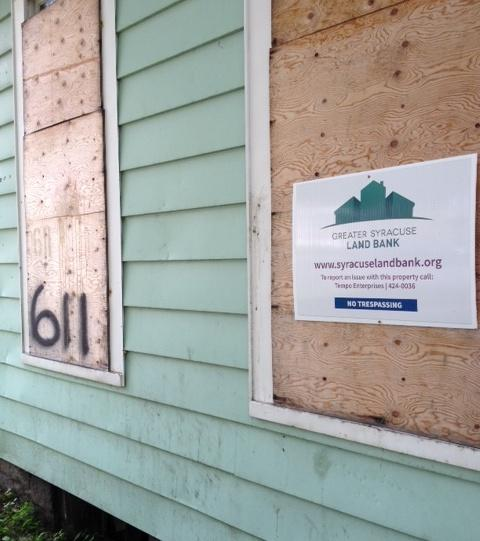 side view of a house with boarded windows and a flier posted to one window board with Syracuse Landbank logo