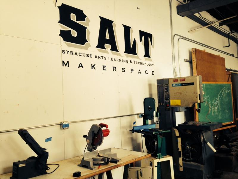 wall with SALT makerspace decal, surrounding by saws and wood working equipment