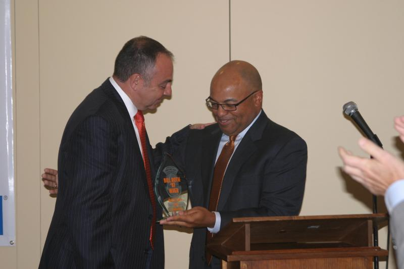 Mike Tirico presents award to Bill Roth