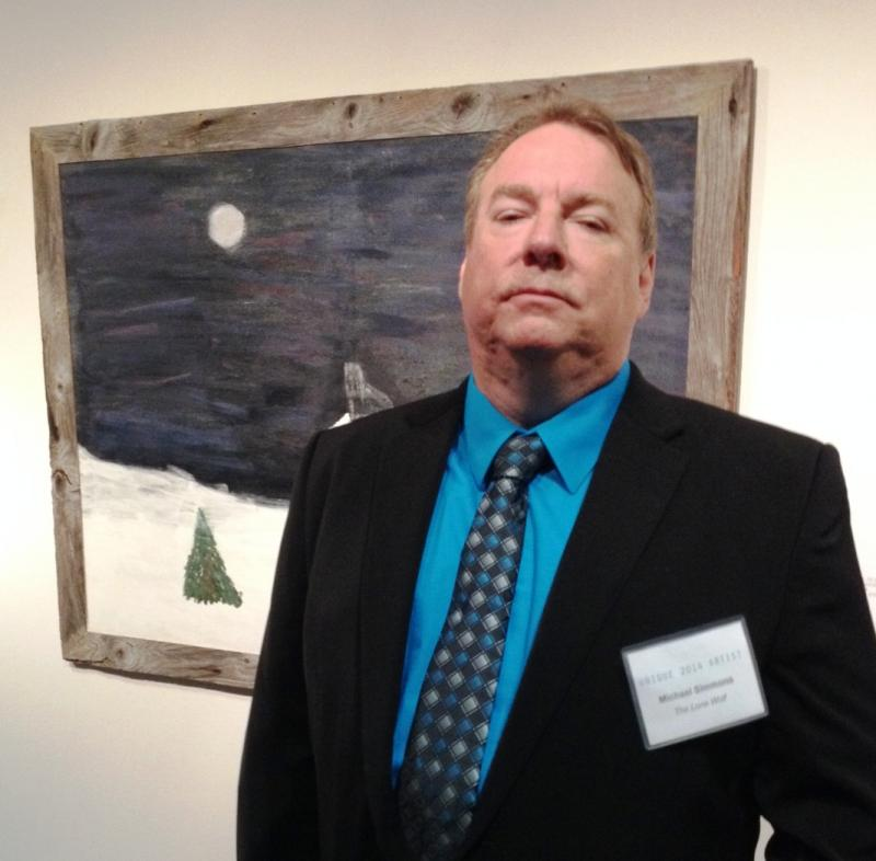 "Artist Michael Simmons in front of his oil painting ""The Lone Wolf."""