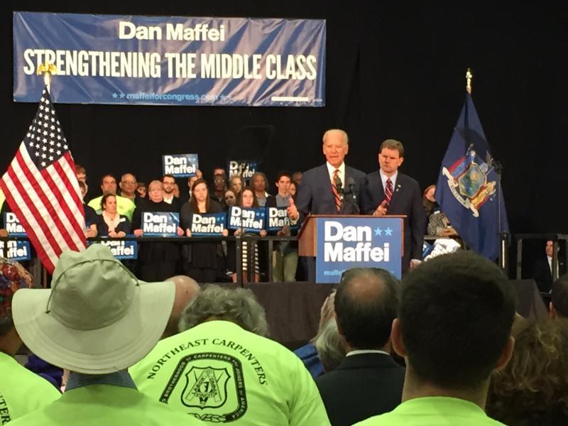 joe biden speaks at a podium in a large, dark room with Congressman Maffei behind him