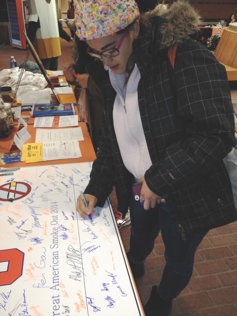Another student signs the banner supporting a Smoke-Free Syracuse campus. More than 100 had signed early Thursday afternoon.