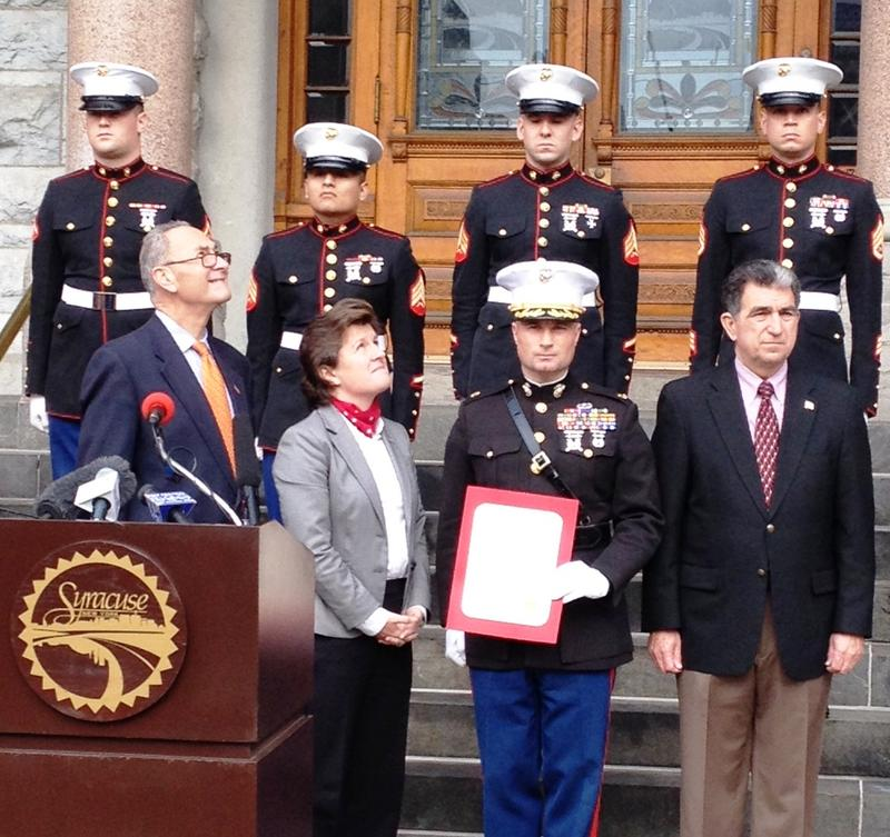 Sen. Schumer, Mayor Stephanie Miner, a marine, and Assemblyman Bill Magnarelli watch the flag go up.