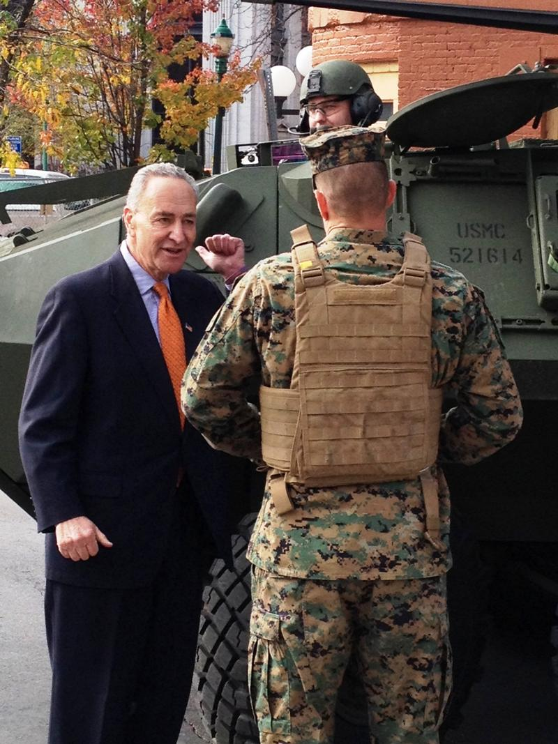 Sen. Chuck Schumer talks to the marines in charge of driving the light armored vehicle brought to Syracuse City Hall to mark the Marines 239th Birthday.