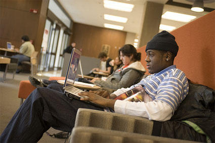 students sit working on laptops