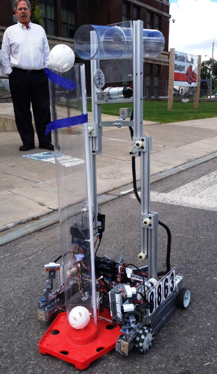A robot made by the First Tech Challenge from Tully shoots a wiffle ball into a tube.