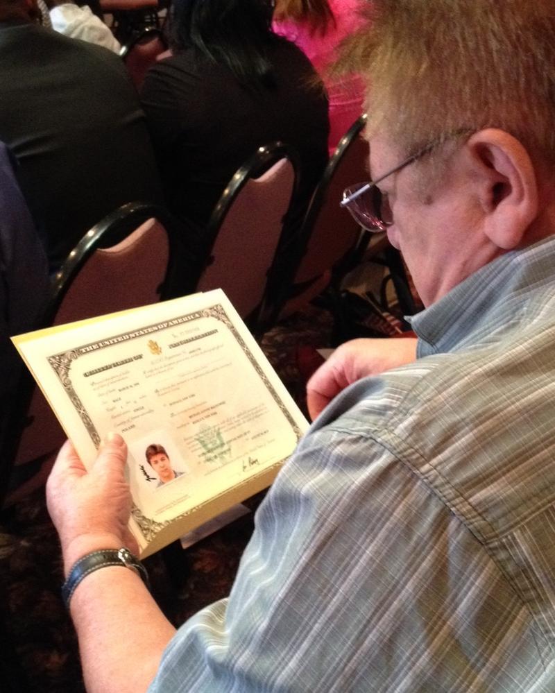 Christopher Rybak looks at hsi grandson's citizenship certificate.