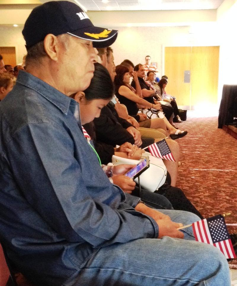 Families listen to remarks at the naturalization ceremony.