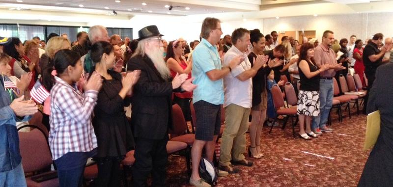 The new citizens and their families applaud after taking the oath.