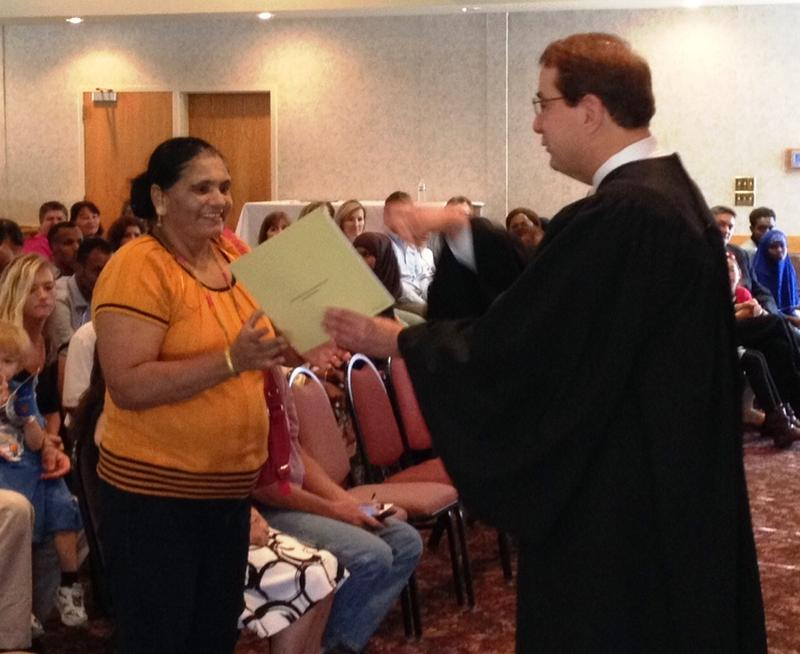 Acting Supreme Court Justice Michael Hanuszczak presents a certificate of citizenship to a new citizen.