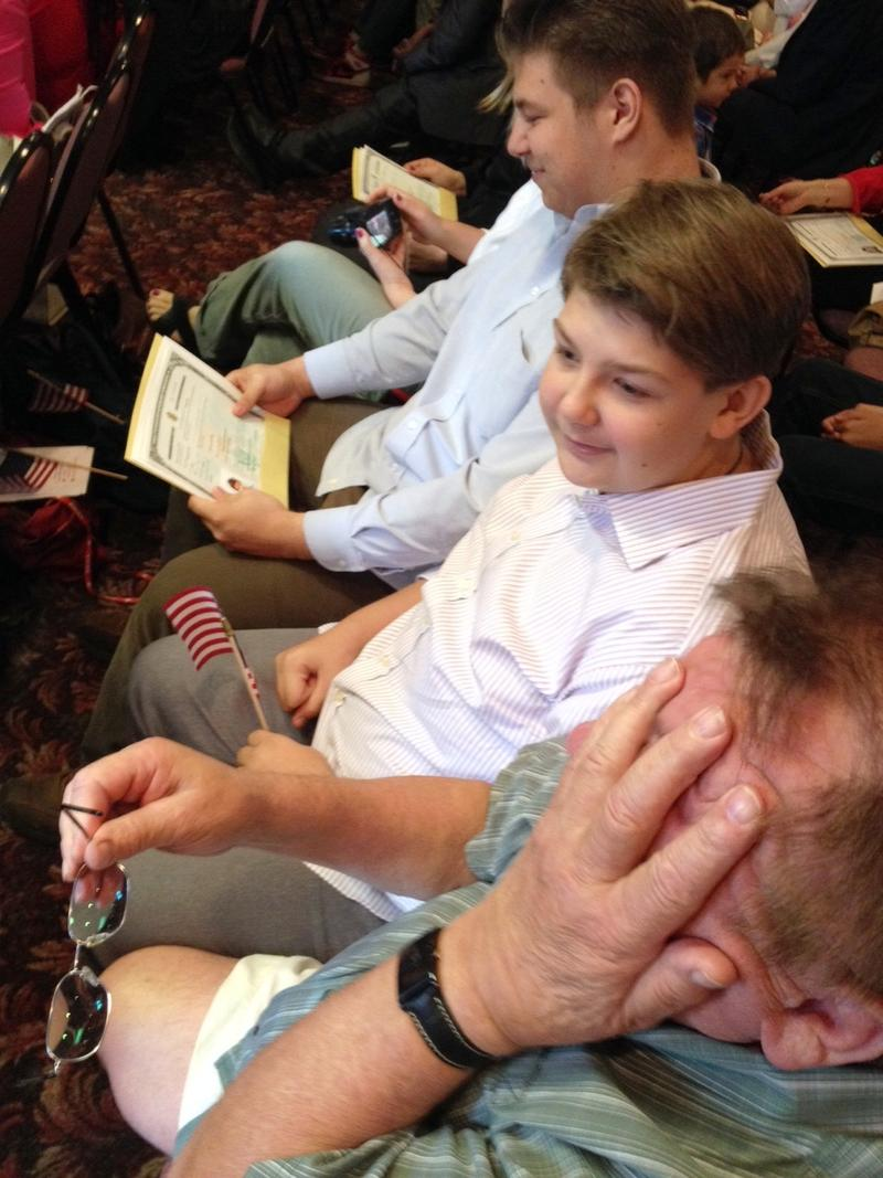 19-year-old Michael Malinowski, formerly of Poland, looks proudly at his certificate of citizenship.  He was joined by his brother and  grandfather Christopher Rybak, who wipes tears from his eyes.