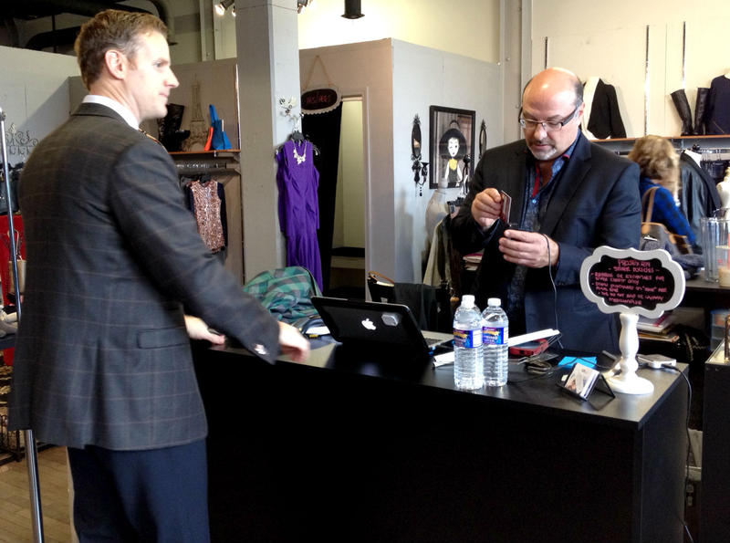 Owner of Projex 214  John Massarah, right, helps a customer at his store's grand opening in downtown Syracuse Thursday.