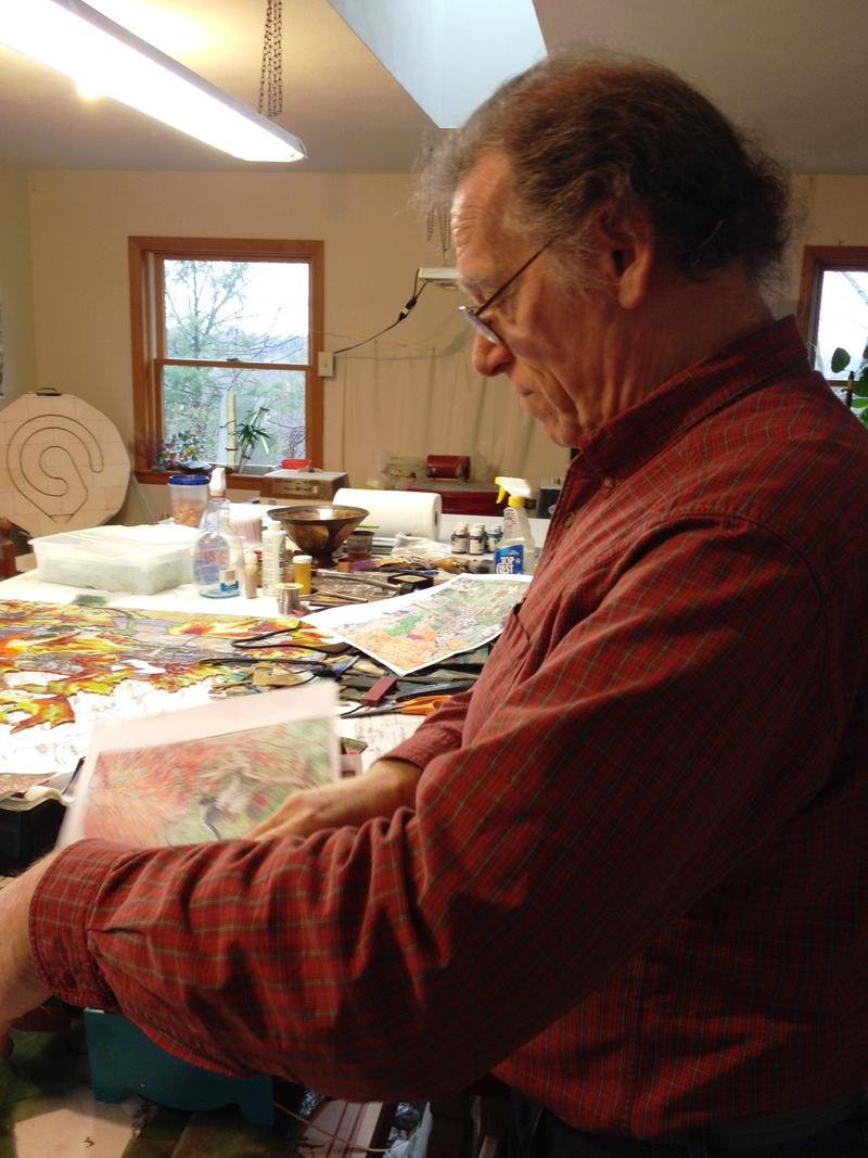 Robert Oddy looks over sketches of his current project in his studio in Syracuse.