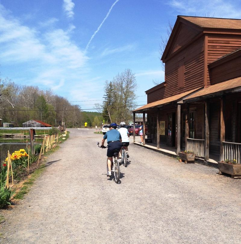Bicyclists pass by Sims Store along the Erie Canlway Trail in Camillus.