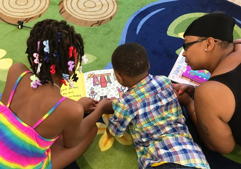 Tahnia Rice reads a book to her brother, Toyree, and mother Shalika in the children's world section of the central library.
