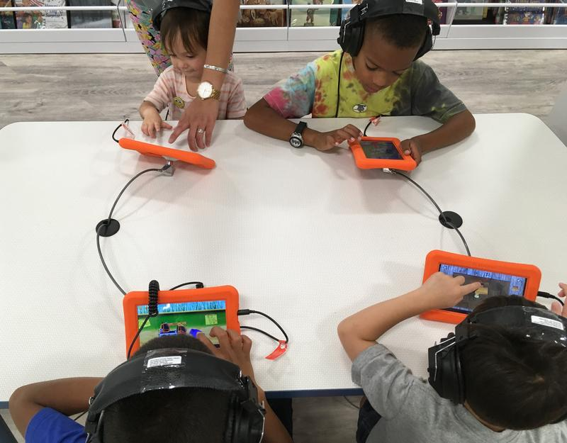 Young children play on tablets.