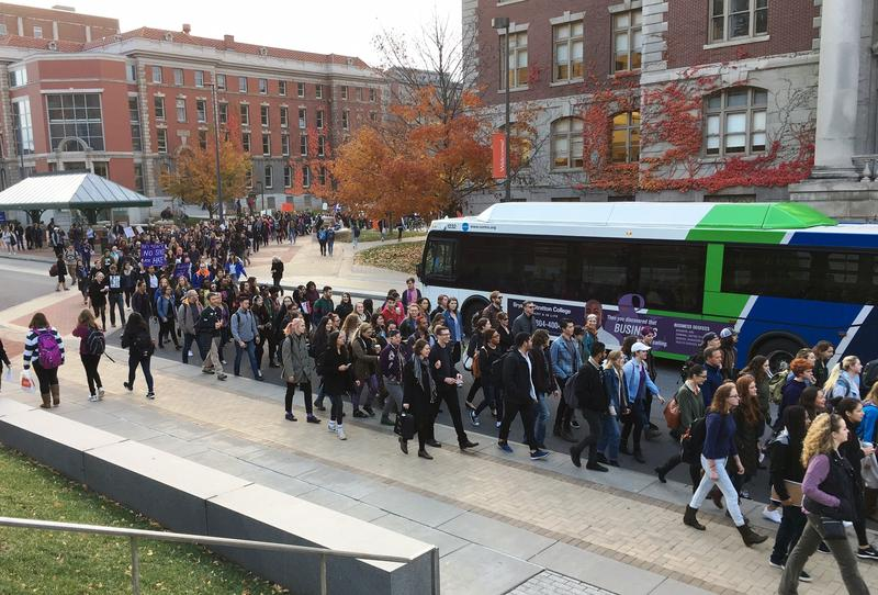 The crowd makes its way down College Place, forcing a bus to wait until they crossed.