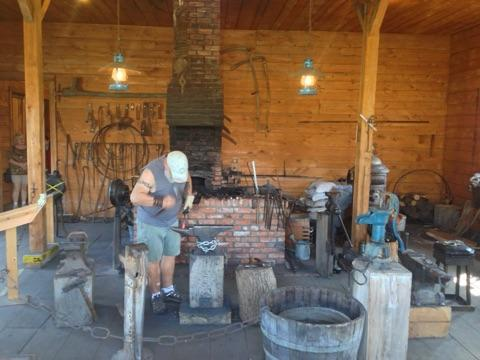 Blacksmith Mike Allen pounds out a creation with hot metal.