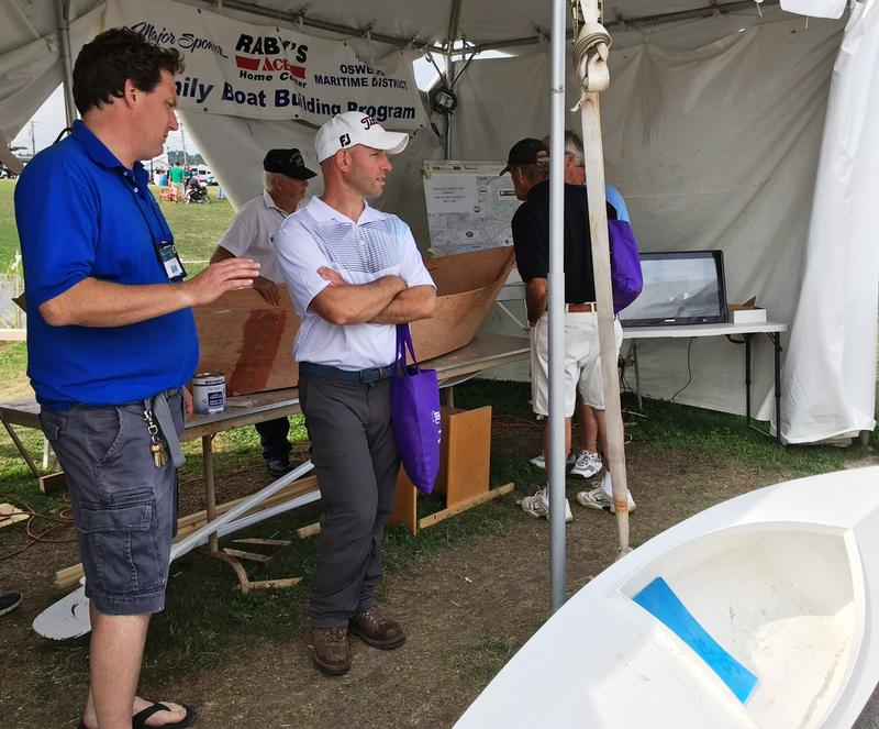 Richard Bush, left, chats with a curious fairgoer at the boat building tent.