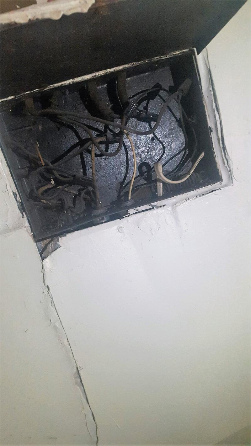 Exposed wires in a stairwell.