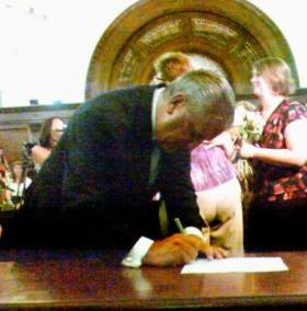 Albany Mayor Jerry Jennings signs documents for a same-sex couple during midnight hour marriages July 2011 at City Hall.