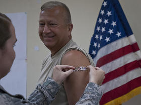 Brig. Gen. Bud R. Jameson Jr. and Command Sgt. Maj. Michael Bolduc lead the Soldiers of the 316th ESC by being the first tp get flu shots from the members of the 316th Surgeon Cell at Camp Arifjan, Kuwait, Sept. 19, 2012.