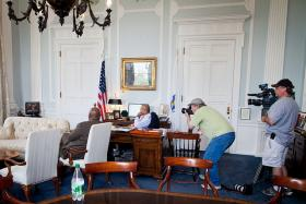 Thursday, June 28, 2012 – Governor Deval Patrick and his chief of staff, Mo Cowan, watch the president address the Supreme Court's ruling on the Affordable Care Act from the Governor's Office while members of the media photograph.