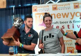 Michael Benz, Brewery Ambassador and pub manager Lauren McFadyen, both of Peekskill Brewery, pose with the Governor's Cup after winning best beer in the state for their Higher Standard Triple IPA.