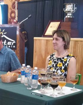 New York State Senator Cecelia Tkaczyk awaits her turn to taste and present the Governor's Cup, pictured behind her, to the best beer in the state at TAP New York 2013.