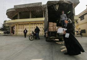 A Syrian refugee who fled the violence in Syria holds a box of food released by the Lebanese community for help at a temporary home in a school at Wadi Khaled area in northern Lebanon