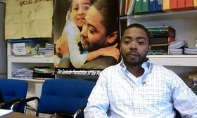 Charles Wilhite of Springfield,MA at a news conference where his civil rights attorney announced the filing of a lawsuit against two Springfield police detectives. Behind Wilhite is a poster showing him hugging his daughter after he was released from prison in 2013