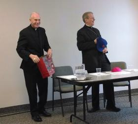 Bishop Hubbard brought a gift-bag to the press conference: here he had just passed the traditional 'red cap' along with a NY baseball cap to Bishop-elect Scharfenberger