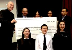 Bishop Howard Hubbard (L) presented Dr. Carolyn Woo (Center) with a $310,000 check for typhoon relief.  (Officials and students also appear in the photo).