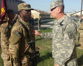 New York National Guard Command Sgt. Major Frank Wicks (right) [promotes 1569th Transportation Co. Soldier Ronald Walker to sergeant prior to the company's deployment to Afghanistan Tuesday.