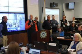 US Secretary of Homeland Security Jeh Johnson addresses people at the Multi-Agency Coordination Center for the 2014 Boston Marathon at the Mass. Emergency Management Agency